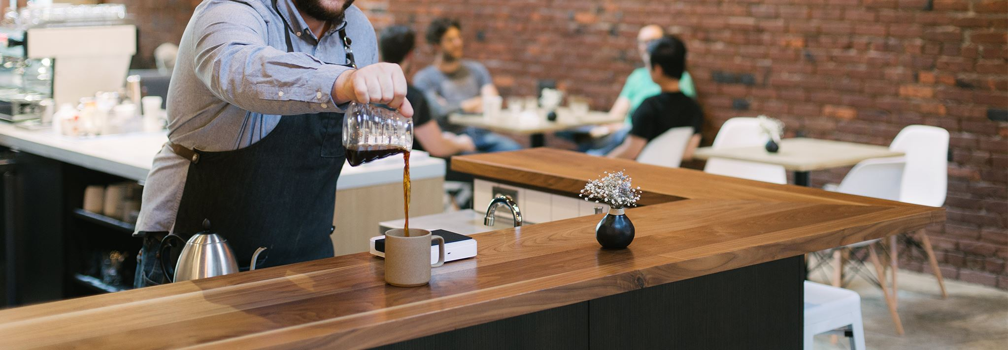 A barista pours coffee at Narrative Coffee